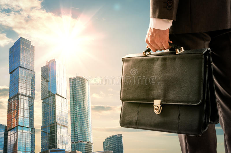 Businessman standing with back against city stock photography