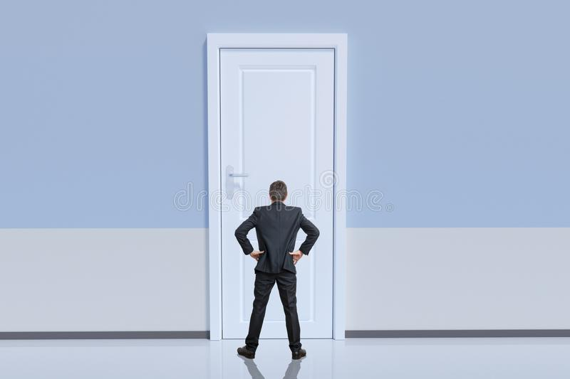 Businessman is standing behind big door. Opportunity and challenge concept.  royalty free stock image
