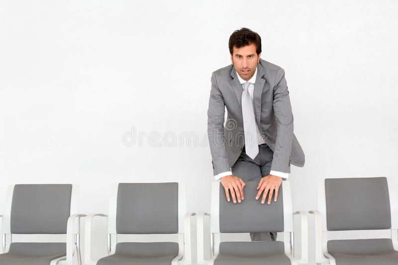 Businessman standing by chairs in waiting room. Man standing by chairs in waiting room stock photography