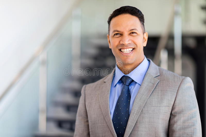 Businessman standing. Cheerful businessman standing by stairway royalty free stock photo