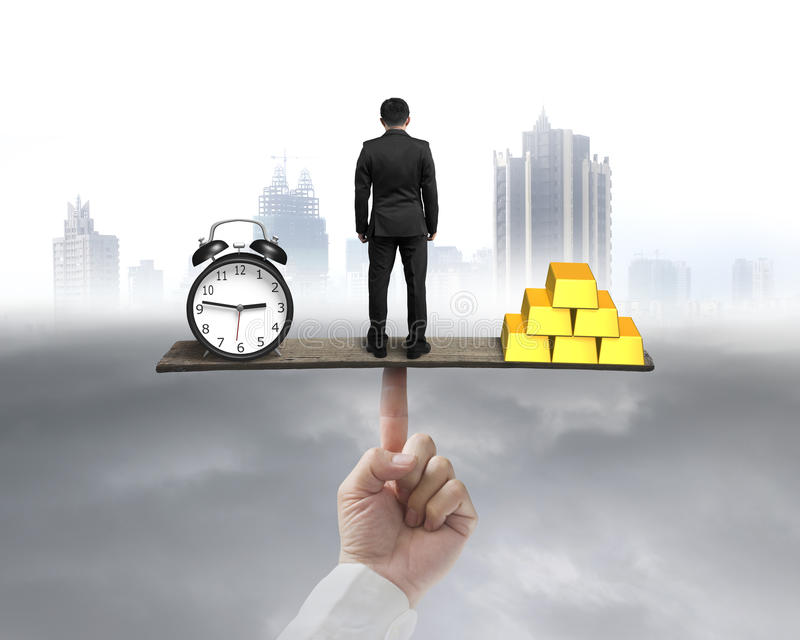 Businessman standing between clock and gold balancing on seesaw. With city background royalty free stock photo