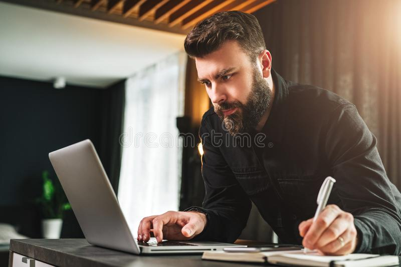 Businessman is standing by computer, looking at laptop screen, making notes in notebook. Man watching webinar, learning. Young bearded businessman is standing royalty free stock photo