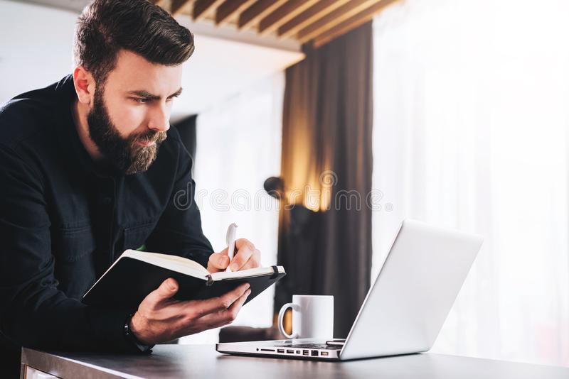 Businessman is standing by computer, looking at laptop screen, making notes in notebook. Man watching webinar, learning. Young bearded businessman is standing stock photos