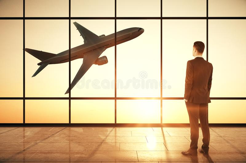 Businessman in creative airport interior. Businessman standing in creative airport interior with flying by airplane and sunlight view in panoramic window royalty free stock photo