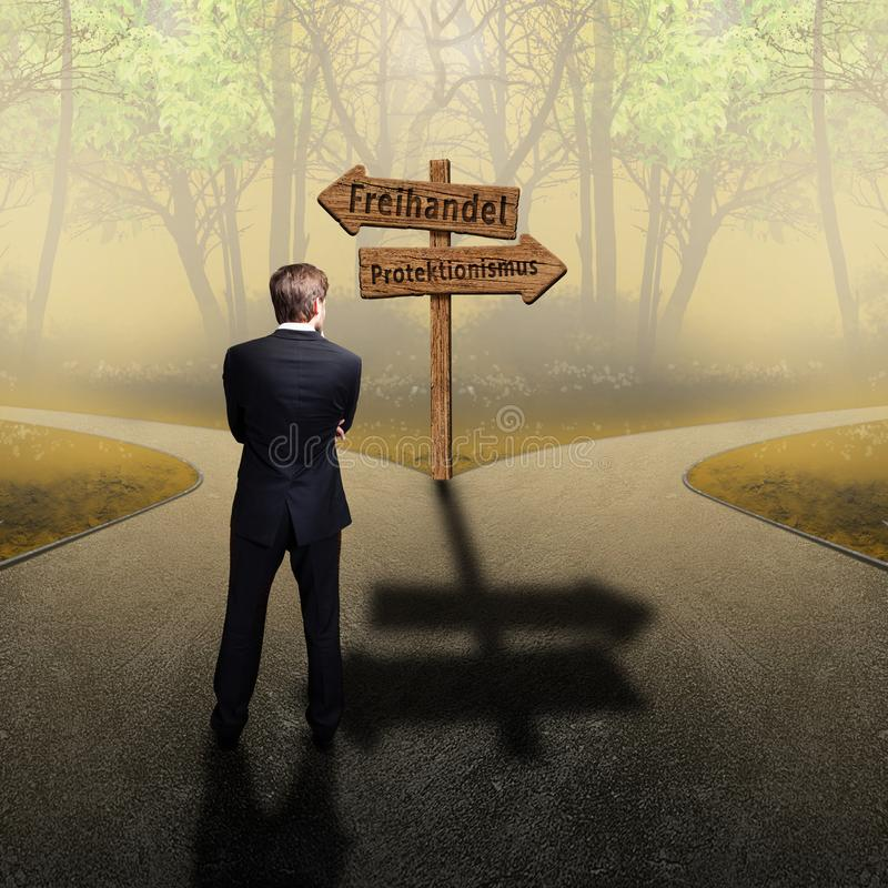 Businessman standing at crossroad having to decide between `free trade` and `protectionism` with road signs in German. Businessman standing at a crossroad having stock images