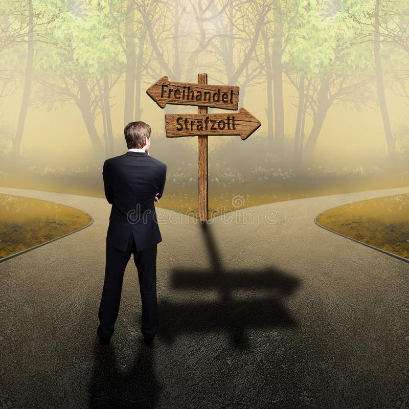 Businessman standing at a crossroad having to decide between `free trade` and `tariffs` on road signs in German royalty free stock photography