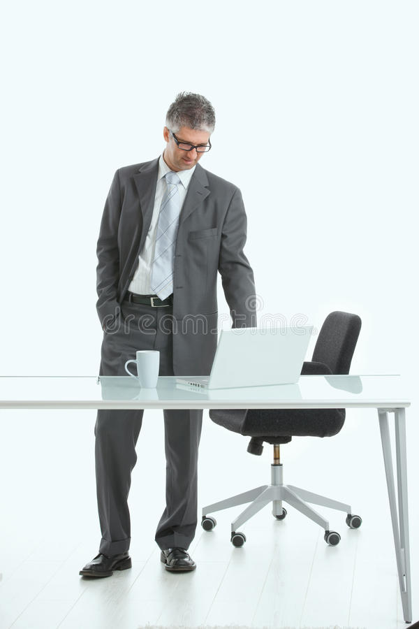Businessman standing at desk stock photo