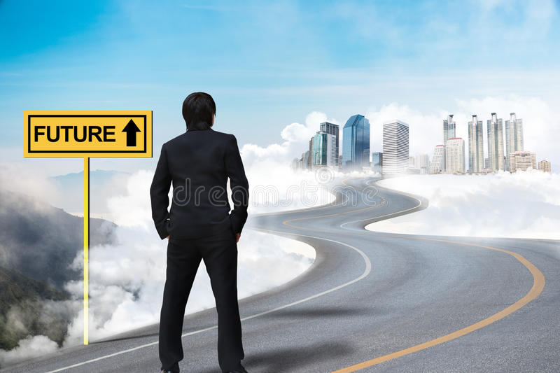 Businessman standing on the empty road. And watching the future city on the cloud stock photo