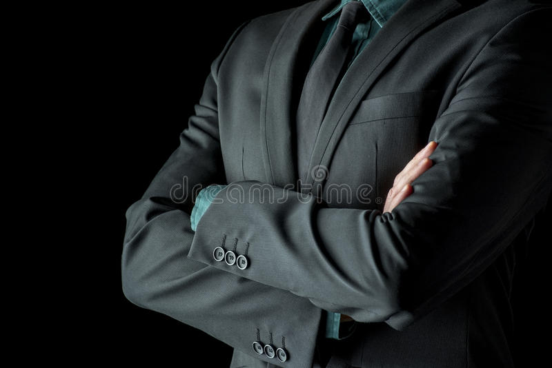 Businessman standing with folded arms in a classic black suit stock image