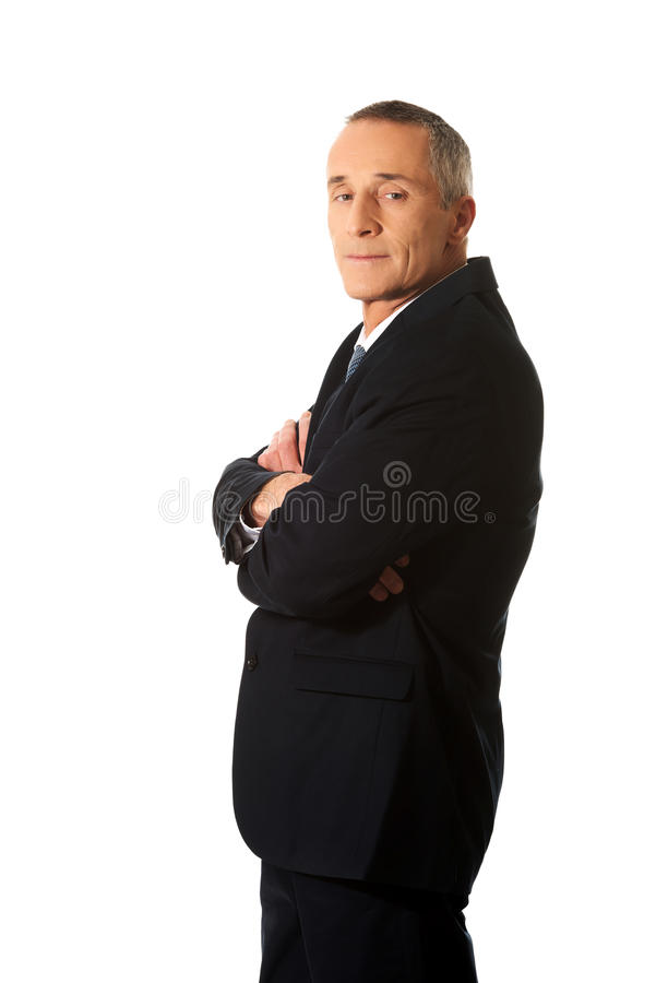 Businessman standing with folded arms. Confident businessman standing with folded arms stock photos