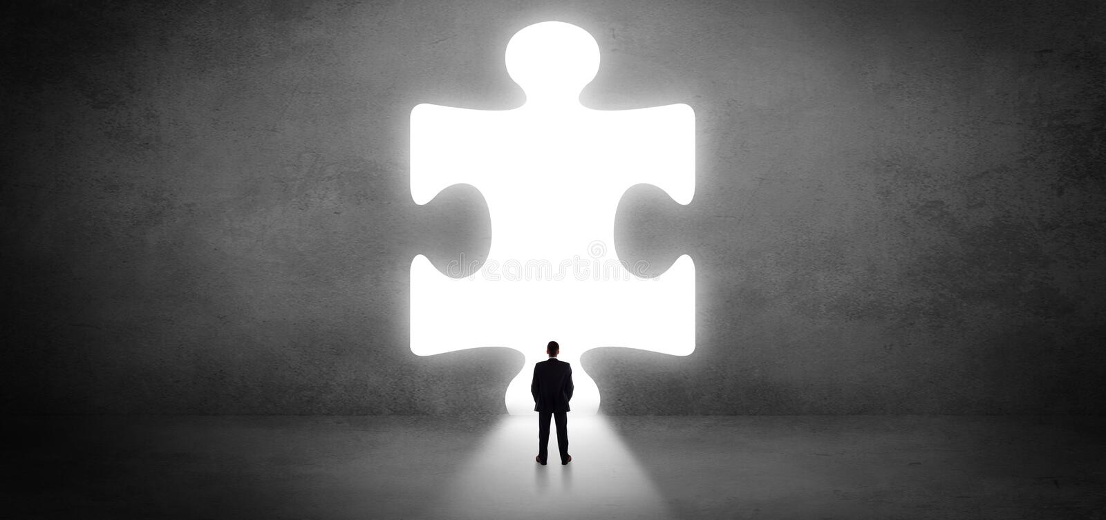 Businessman standing in front of a big puzzle piece royalty free stock images