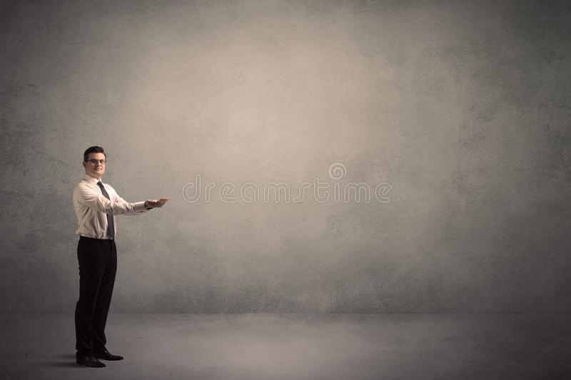 Businessman standing in front of a blank wall stock photo