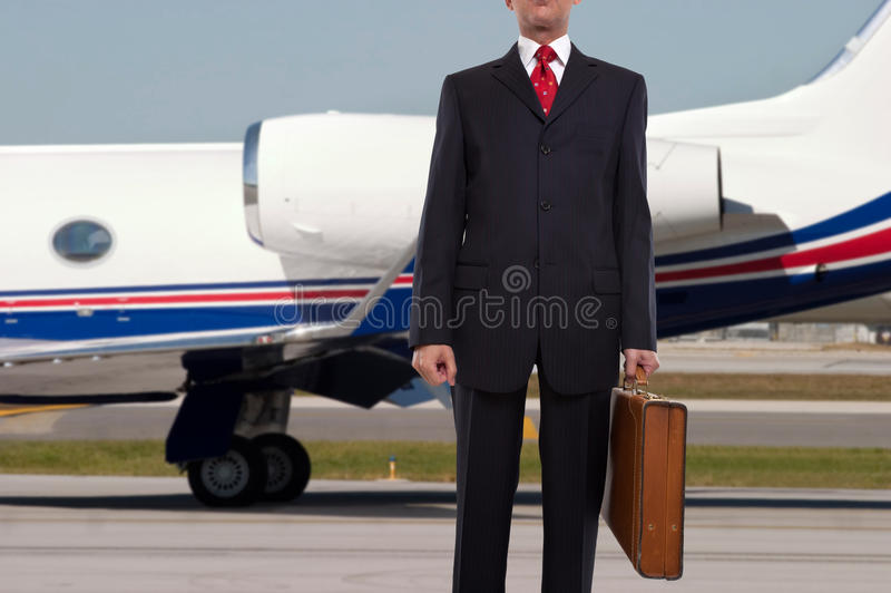 Businessman standing in front of corporate jet stock images