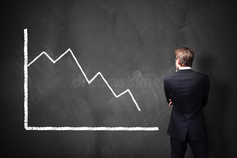 Businessman standing in front of a decreasing chart on a blackboard royalty free stock photography
