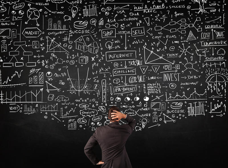 Businessman standing in front of drawn charts on a blackboard royalty free stock image
