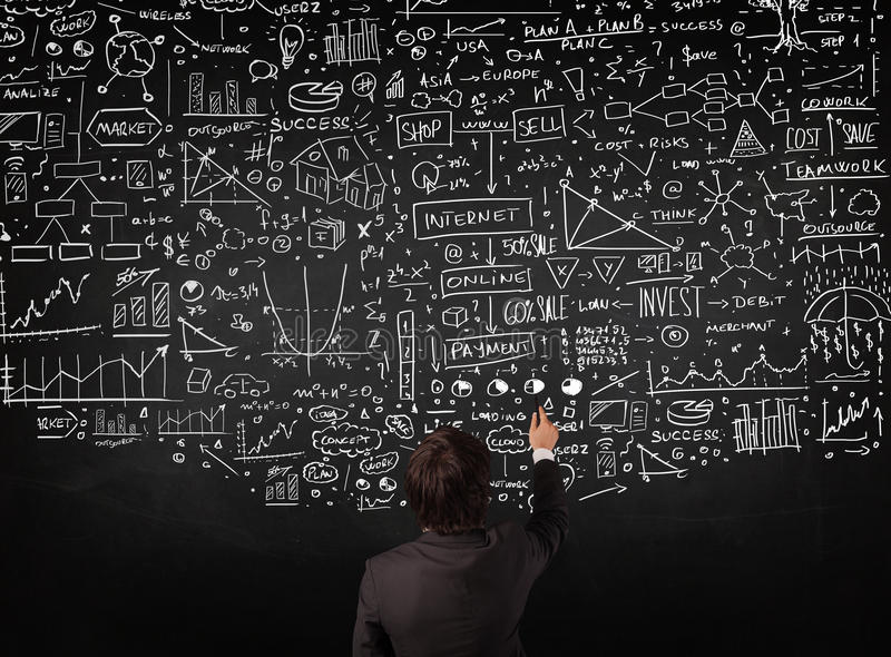 Businessman standing in front of drawn charts on a blackboard stock photo