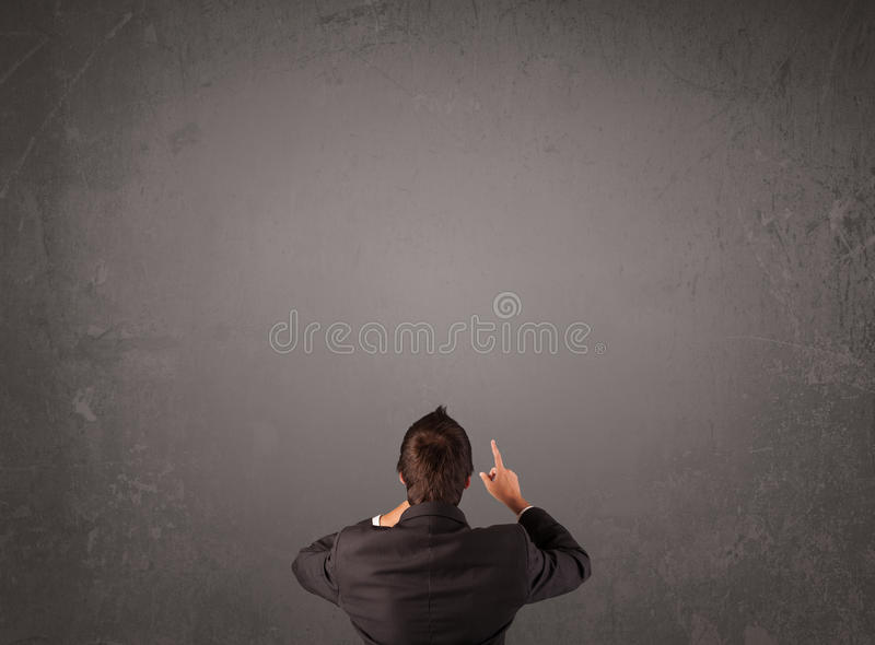 Businessman standing in front of an empty wall royalty free stock photo