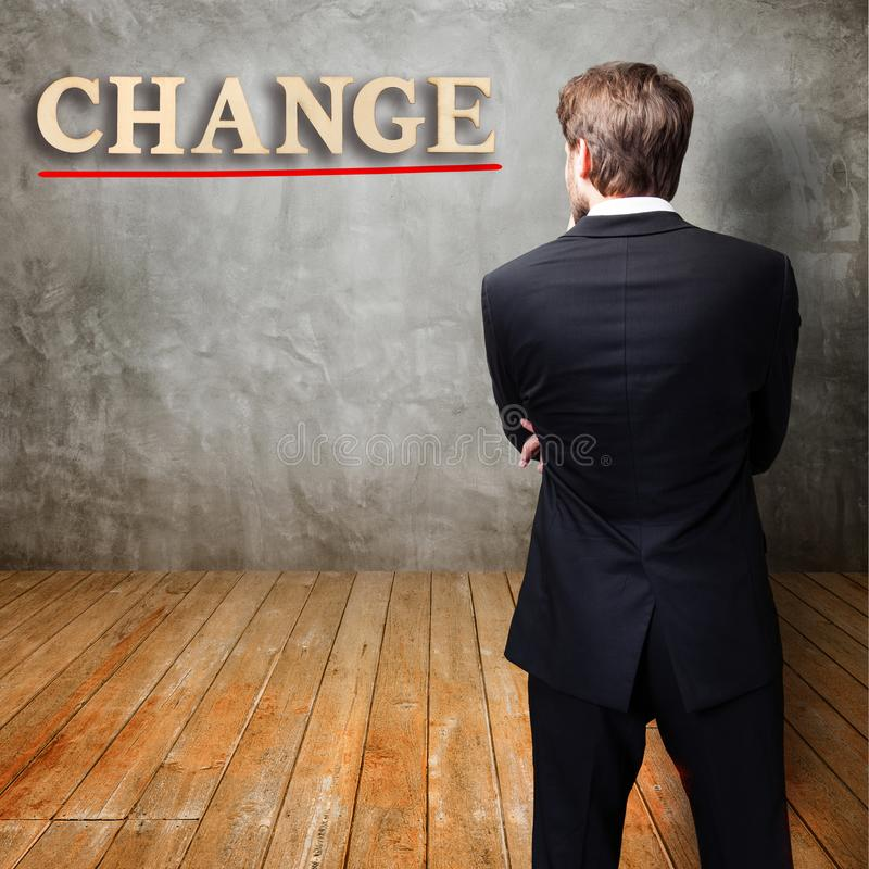 Businessman standing in front of a wall with the message `change` royalty free stock images