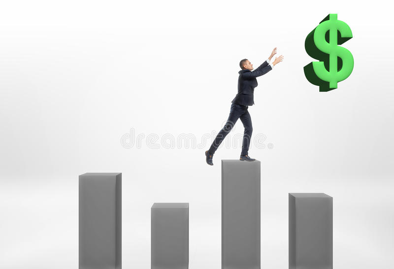 Businessman standing on grey column with his hands up to the big dollar sign stock image