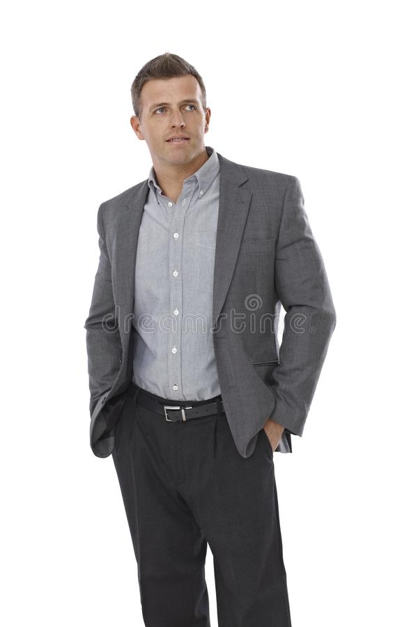 Businessman standing with hands in pockets. Looking away royalty free stock photo