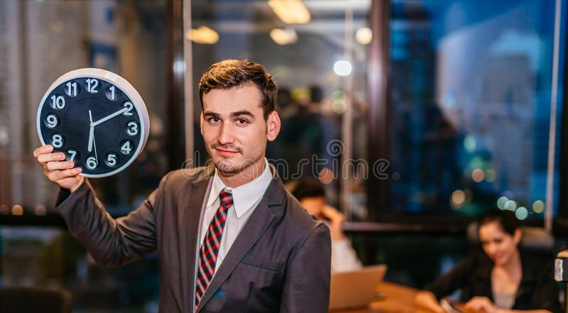 Businessman standing and holding alarm clock office at night late overtime royalty free stock photography