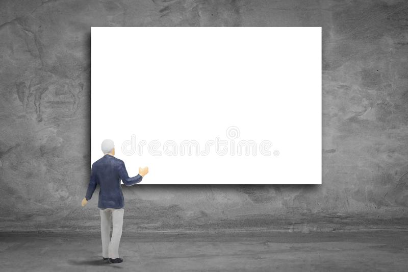 Businessman standing and looking blank billboard hanging on concrete wall. stock image