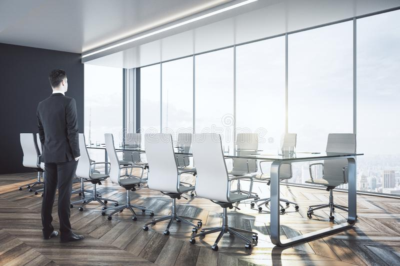 Businessman standing in luxury meeting room. Interior with city view and daylight stock images