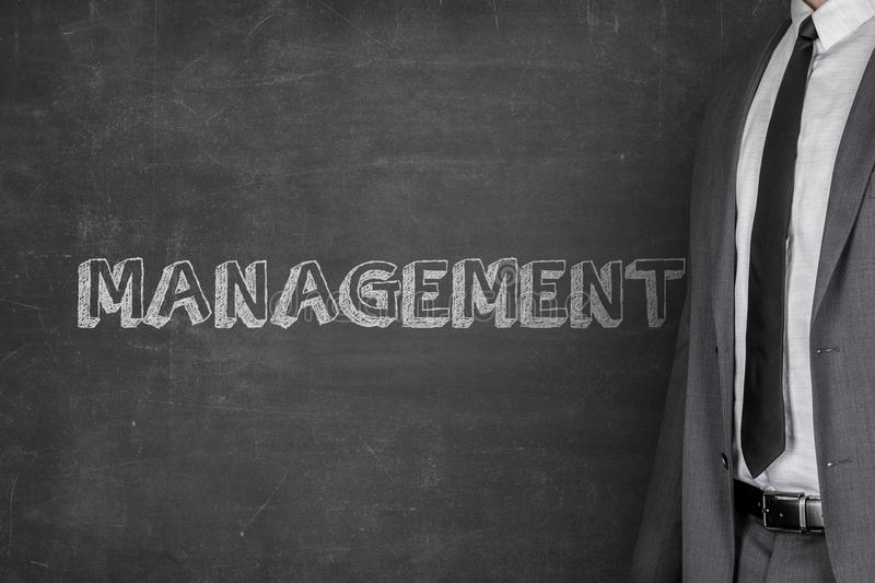Businessman Standing By Management Text On Blackboard. Midsection of businessman standing by management text on blackboard royalty free stock photos