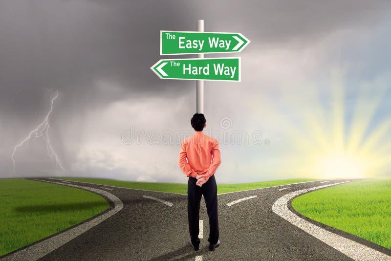 Businessman choosing easy or hard way stock image