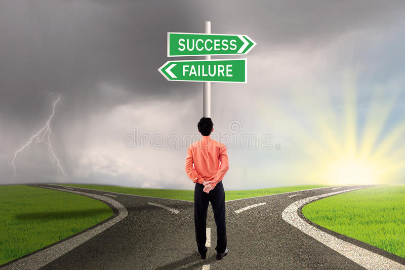 Businessman choosing success or failure road. Businessman is standing in the middle of road signs, choosing between success or failure road stock images