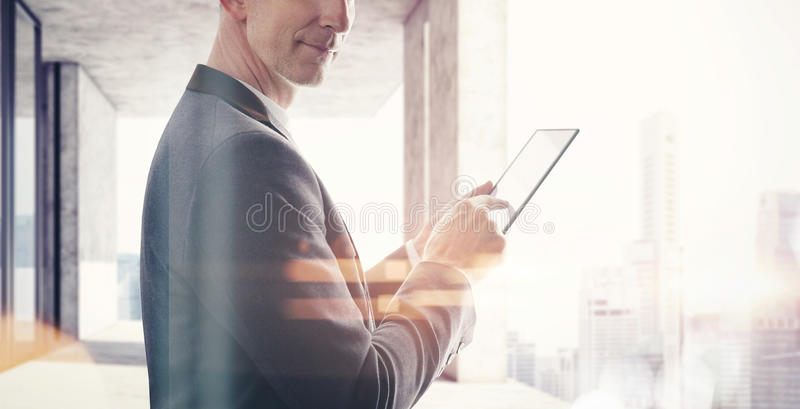 Businessman standing in modern loft and touching screen of tablet. Blurred city background. Wide, visual effects stock photos