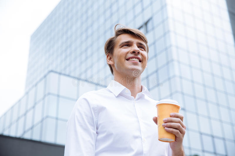 Businessman standing near business center and drinking coffee stock photos