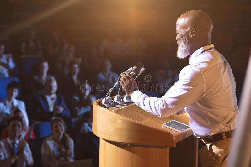 Businessman standing near podium and giving speech to the audience in the auditorium. Side view of old African-American businessman standing near podium and royalty free stock image