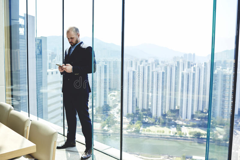 Businessman is standing near window with copy space background for your content. Confident managing director is typing text message on cell telephone, while is stock photos