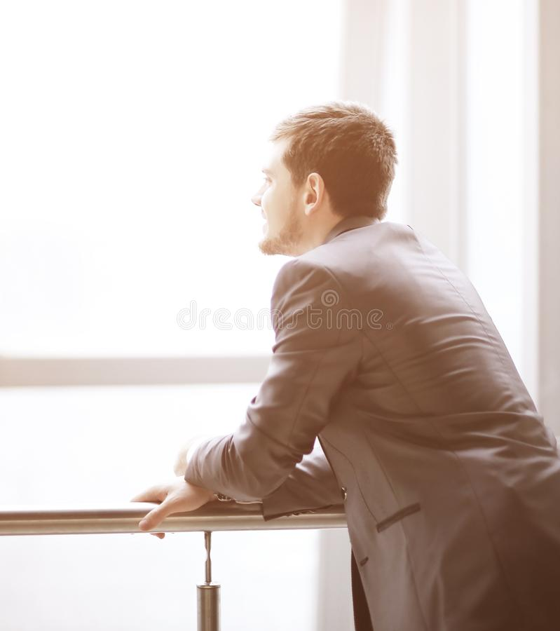 Businessman standing near the window and looking into it stock images