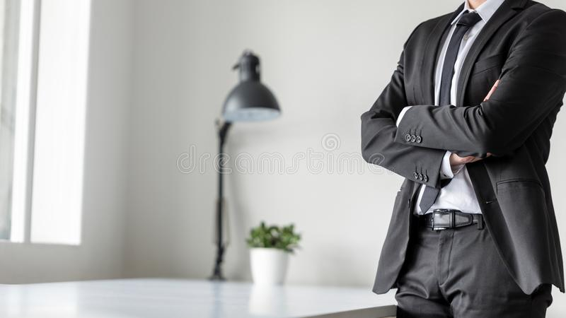 Businessman standing in office with crossed arms stock image