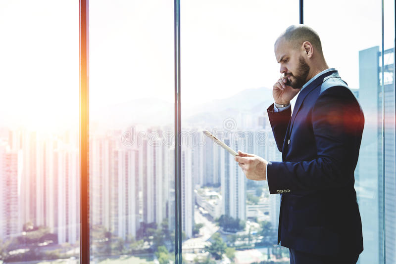 Businessman is standing in office interior near window with copy space area. Furious man professional banker is read in internet via touch pad information about stock images