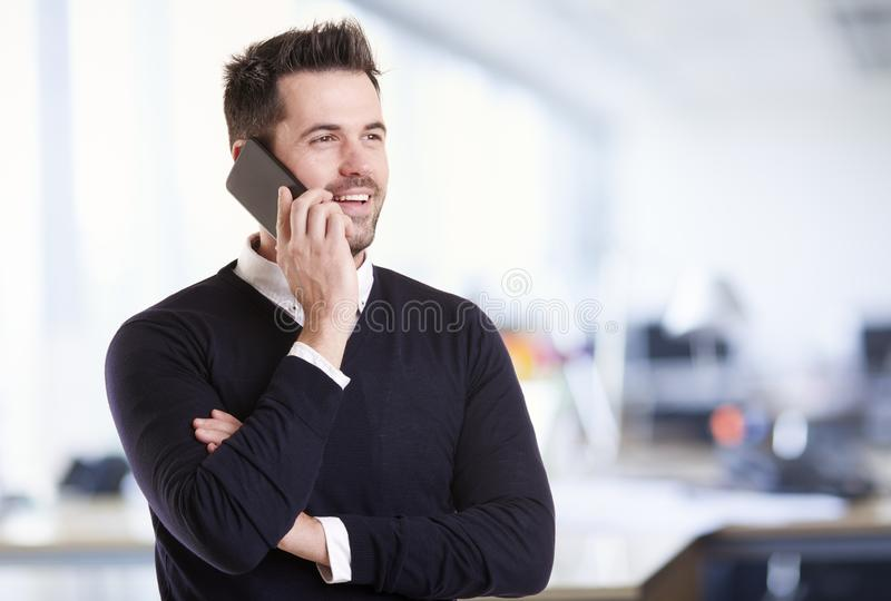 Businessman standing in the office and talking with somebody on his mobile phone stock photo