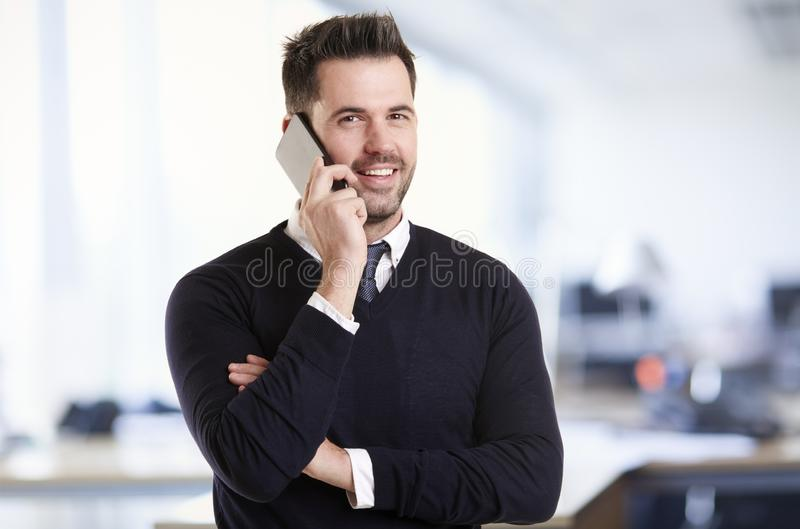 Businessman standing in the office and talking with somebody on his mobile phone stock photography