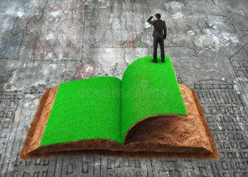 Businessman standing on open book of grass and soil texture. Small businessman standing on the opened book of green grass and soil textured, on dirty doodles royalty free stock image