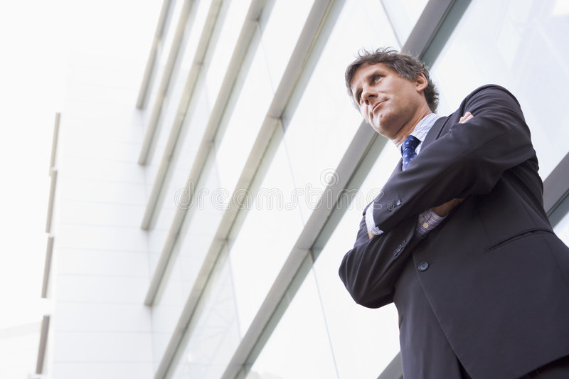 Businessman standing outdoors by building stock photos