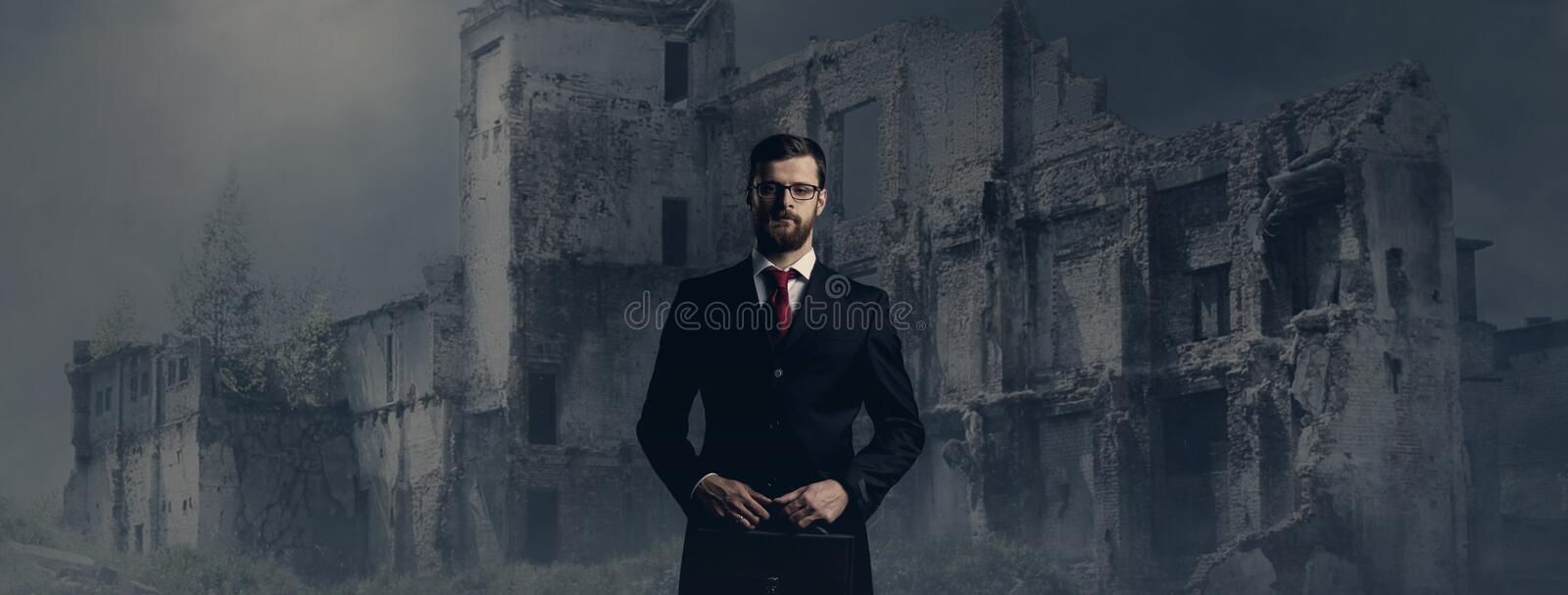 Businessman standing over apocalyptic background. Crisis, default, setback concept. stock photo