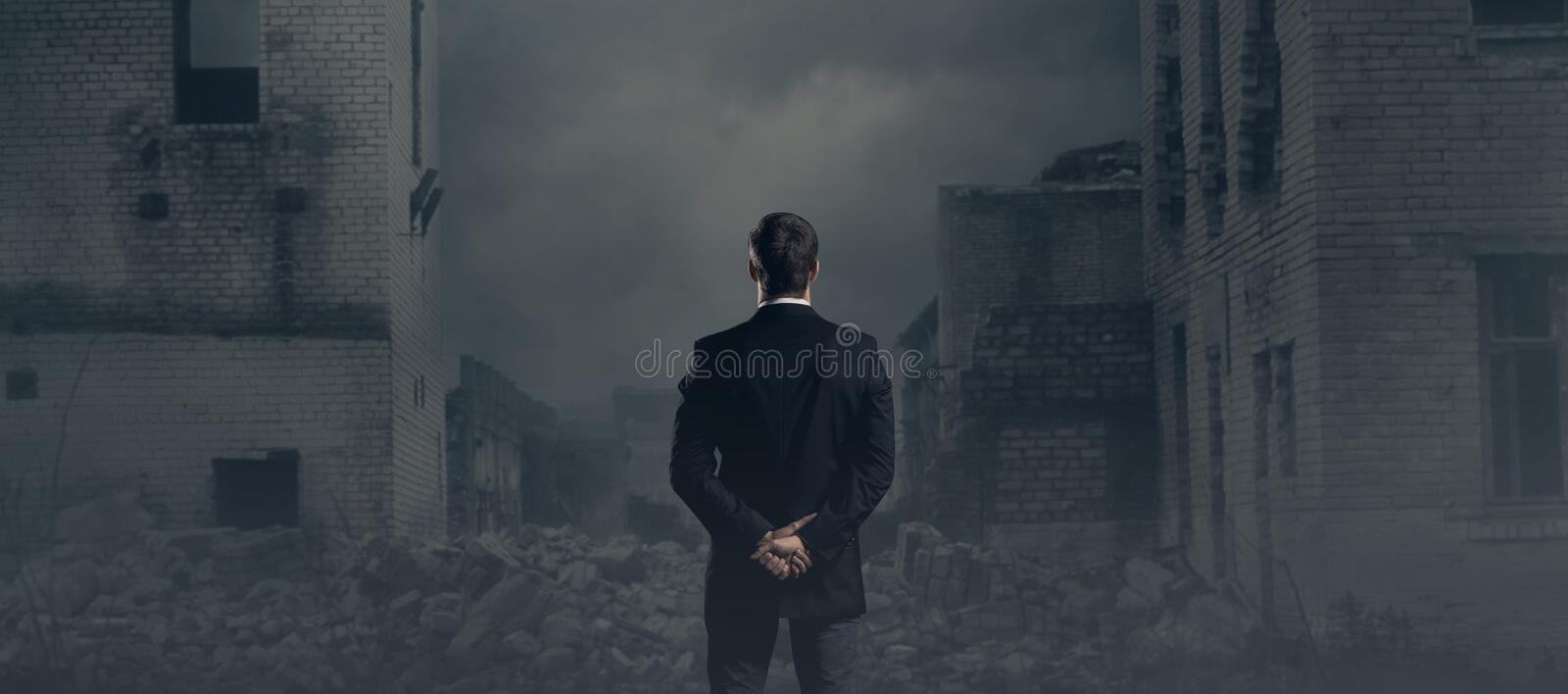 Businessman standing over apocalyptic background. Crisis, default, setback concept. royalty free stock photography