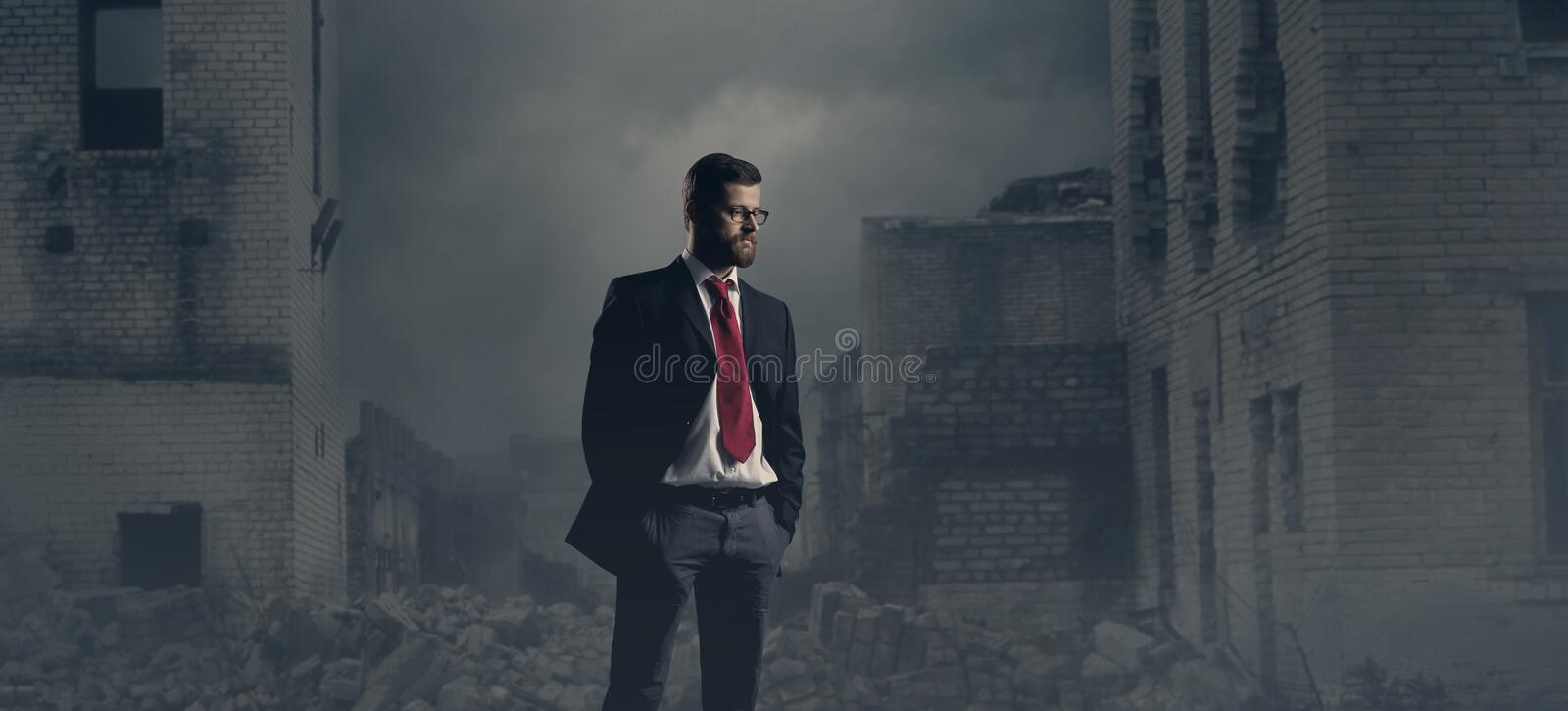 Businessman standing over apocalyptic background. Crisis, default, setback concept. stock photography