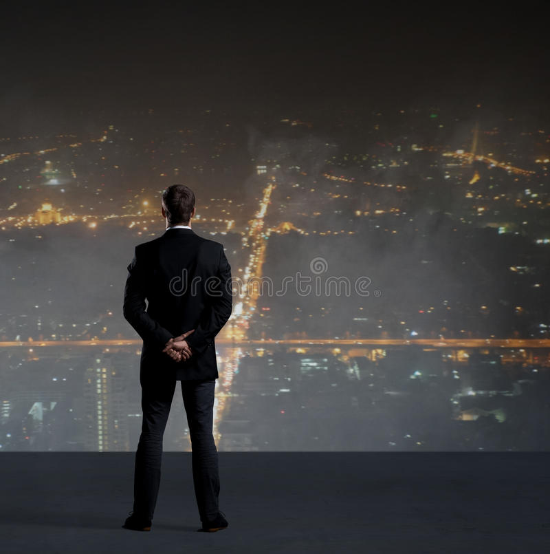 Businessman standing over night city background. royalty free stock photo