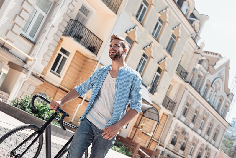 Opportunities don`t happen. You create them. Young brown-haired man standing outdoors with a bicycle and looking away. royalty free stock photo