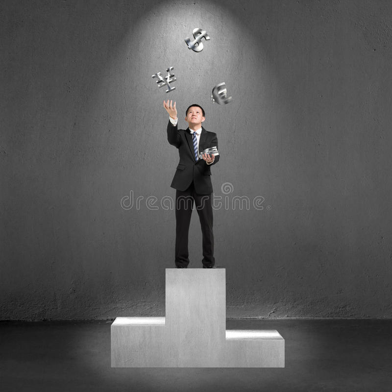 Businessman standing on podium throwing and catching 3D money symbols. Businessman standing on podium throwing and catching 3D sliver money symbols royalty free stock photo