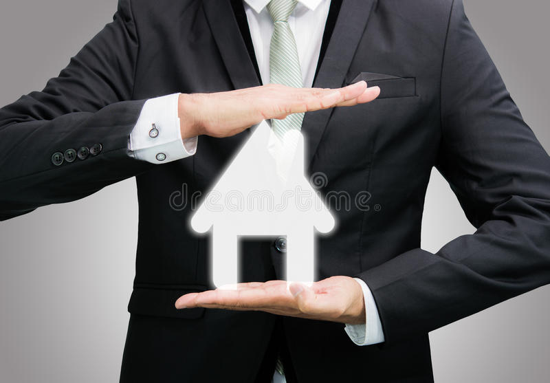 Businessman standing posture hand holding house icon isolated. On over gray background royalty free stock photography