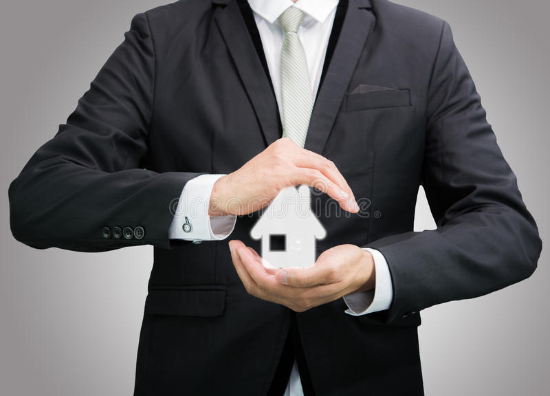 Businessman standing posture hand holding house icon isolated. On over gray background stock photos