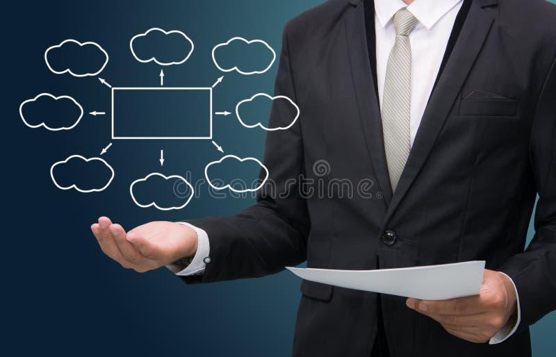 Businessman standing posture hand holding strategy flowchart iso. Businessman standing posture hand holding strategy flowchart on dark background stock photo